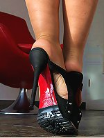 Spicy woman is posing on the leather high heels